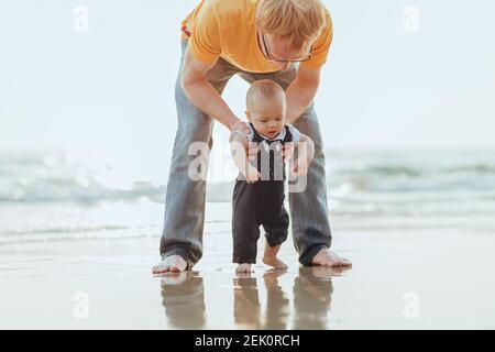 Feliz familia en la playa. Padre, madre y bebé divirtiéndose en las vacaciones de verano. Concepto de viaje de vacaciones