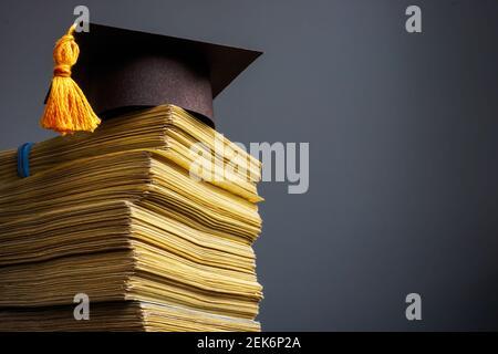 Concepto de costo de la educación. Tope de graduación y pila de dinero para la universidad.