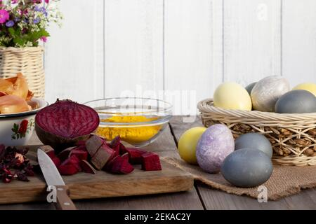Proceso de colorear huevos de Pascua con varios colorantes naturales de la comida. Preparándose para la Pascua