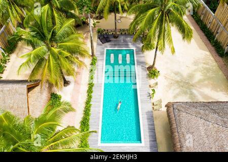 Vista aérea de una chica nadando en una piscina durante el brote de Covid-19.