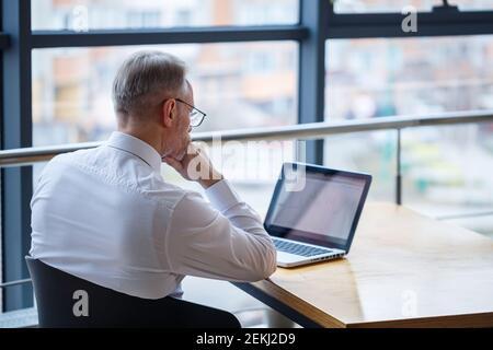 Hombre freelancer está trabajando en un café en un nuevo proyecto de negocios. Se sienta en una ventana grande en la mesa. Mira a una pantalla de portátil con una taza de café