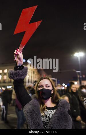 Un manifestante sostiene un rayo rojo - el símbolo de la resistencia de las mujeres polacas durante la manifestación. Fuera del parlamento en la noche del vigésimo noveno día de protestas lideradas por la organización huelga de mujeres (Strajk kobiet), manifestantes contra la sentencia del Tribunal Constitucional que quemaba el aborto, se reunieron de nuevo fuera del Parlamento y comenzaron a marcharse en el centro de Varsovia. Después de las revueltas con la policía, la marcha terminó fuera del edificio de la Televisión Polaca (TVP - Telewizja Polska), donde la policía antidisturbios utilizó spray de pimienta y detuvo a numerosos manifestantes.