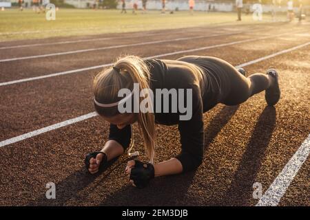 Joven mujer atlética haciendo ejercicio de tabla en pista de correr. Luz de puesta de sol sobre fondo, hermosa perspectiva.