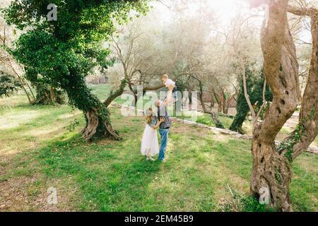 Feliz familia - mamá, papá y el pequeño hijo juntos en el olivar, papá levanta al bebé en sus brazos Foto de stock