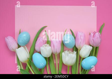 Semana Santa. Tulipanes rosados y blancos flores y azul Pascua huevos decorativos sobre un fondo rosa claro. Fondo festivo de Pascua en colores pastel
