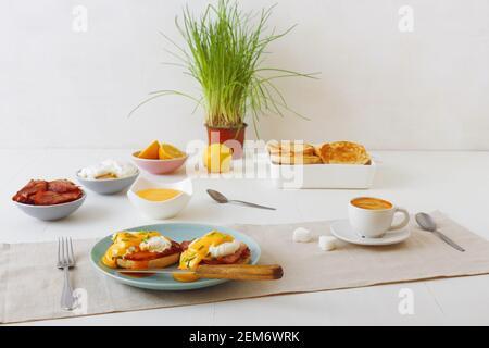Huevos Benedict, muffins ingleses, jamón a la parrilla, huevos escalfados, salsa holandesa, hierbas de cebolleta, limón, taza de café. Mesa de madera blanca con desayuno. Lo