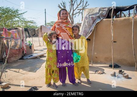 Rajastán. India. 07-02-2018. Madre con dos hijas en un pequeño pueblo de la India durante la puesta de sol. Foto de stock
