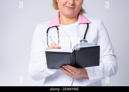 Fotografía recortada y de cerca de la enfermera femenina escriba a mano la anamnesis del paciente en el diario médico en el lugar de trabajo, la mujer médico o las notas del médico llenar la clínica