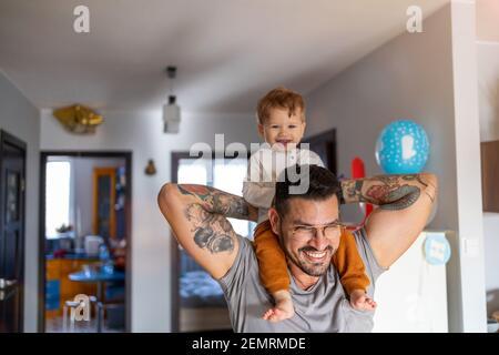 Padre feliz llevando a su hijo sobre el hombro mientras está de pie en casa