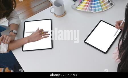 Agrupe al diseñador gráfico utilizando una tableta digital y planificando su proyecto en una oficina creativa.