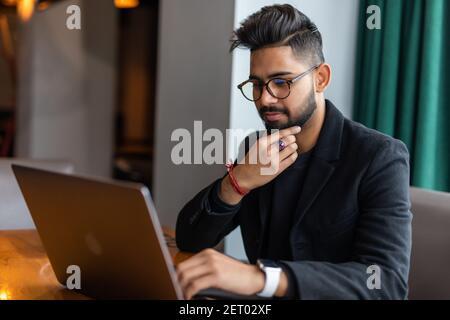 Joven asiático trabajando con el ordenador portátil mientras bebía café en el espacio de trabajo.