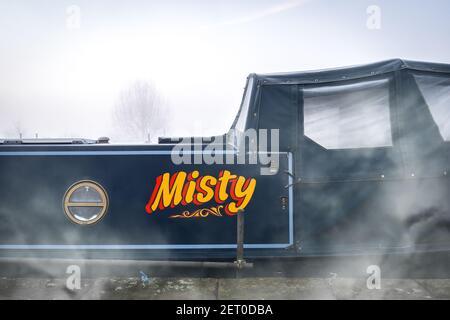 Misty River Boat había pintado texto de escritura con niebla visible que se elevaba del canal a lo largo del lado de la casa azul narrowboat. Los árboles de la mañana foggy silueted
