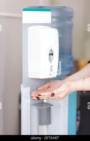 Primer plano de la mano de la mujer usando un dispensador automático de alcohol para limpiar la mano en el hospital. Concepto de prevención de infecciones. Guardar y limpiar en público m