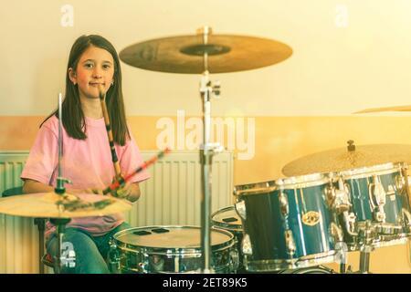 Chica feliz en terapia musical tocando kit de batería en la sala de música. Hermosa joven baterista con tambores tocando tambores y platillos. Baterista femenina