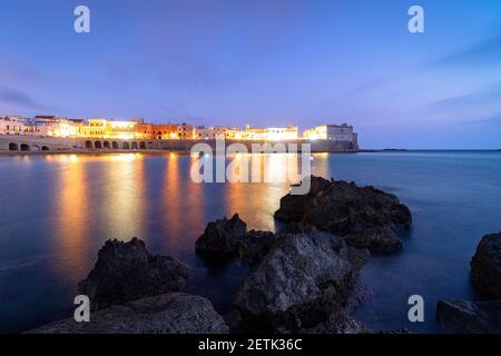 Edificios iluminados de Gallipoli reflejados en el mar azul al atardecer, provincia de Lecce, Salento, Apulia, Italia