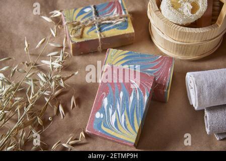 Aromático jabón orgánico multicolor hecho a mano y artículos de cuidado personal hechos de materiales naturales sobre un fondo marrón. Foto de stock