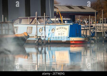 Trent Lock, Nottingham Feb 29th 2021 Morning Mist River Boat pintado texto de escritura con niebla visible que se eleva desde el canal a lo largo del azul narrowboat