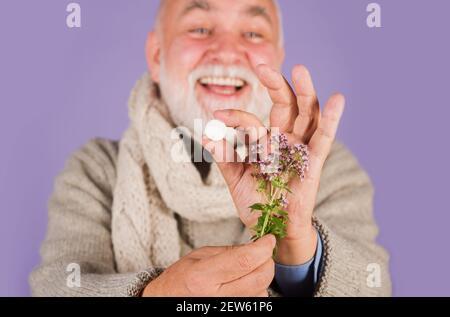 Hierbas medicinales, sanidad, productos farmacéuticos y homeopatía. Hombre con pastillas y plantas herbarias.