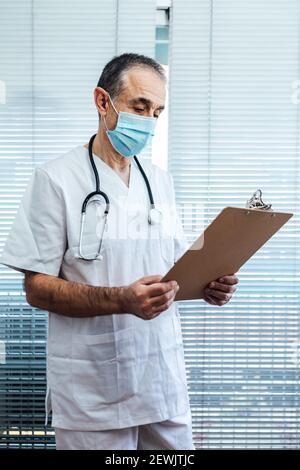 Médico masculino maduro - enfermera con máscara facial, hablando por teléfono móvil y sosteniendo un informe junto a una ventana del hospital. Covid-19 y concepto de medicina.