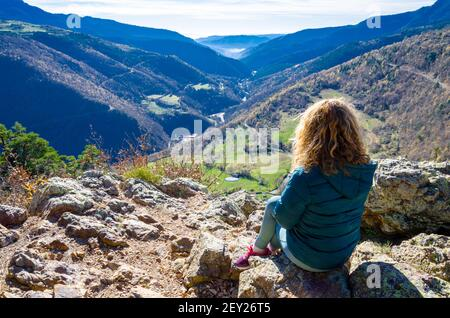 Mujer rubia de pelo rizado, sentada en un banco, mirando las fantásticas vistas de las montañas Ribes, en la región de Ripolles, Girona