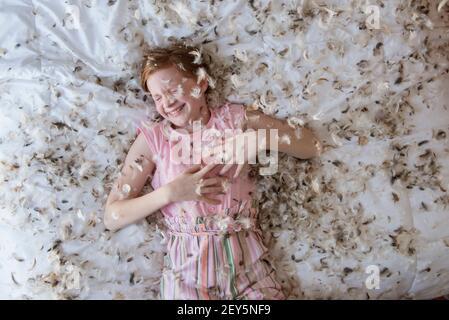 Joven niña de pelo rojo tumbada en la cama durante una pelea de almohadas de plumas. Foto de stock
