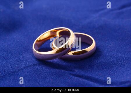 Anillos de bodas de oro. Dos anillos de compromiso de primer plano sobre fondo de terciopelo azul, joyería macro para recién casados.