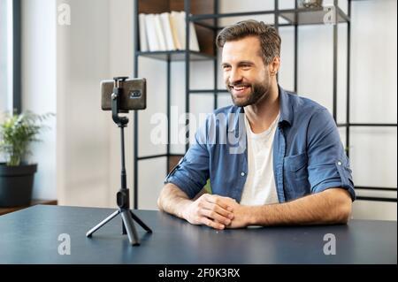 Sonriente hombre guapo hombre blogger, con estilo, sentado frente al teléfono móvil en el estabilizador de trípode grabación streaming de vídeo, compartir la experiencia de compra, recomendar o evaluar el servicio en línea