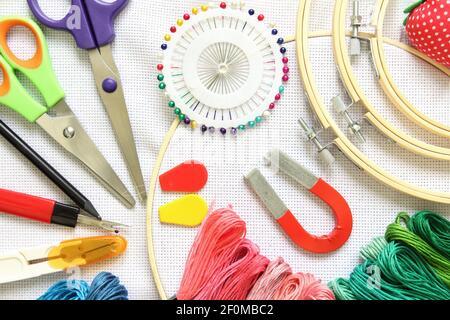 aro de bordado con accesorio de costura, tijeras, hilos de bordado y aguja sobre una tela blanca