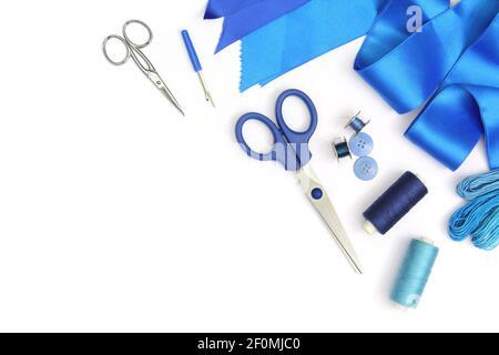 composición creativa con herramientas de costura azul y accesorios cortados y aislados en marco blanco con tijeras, bobinas de hilos y ribbo de tela azul