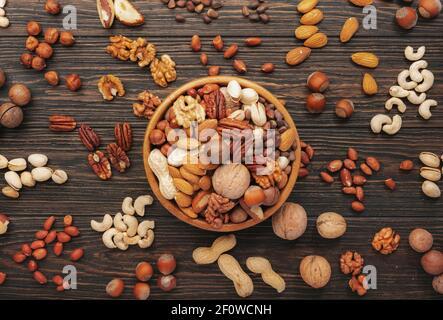 Surtido de frutos secos en cuencos. Anacardos, avellanas, nueces, pistachos, pacanas, nueces de pino, cacahuetes, macadamia, almendras, nueces de brasil. Mezcla de alimentos en madera