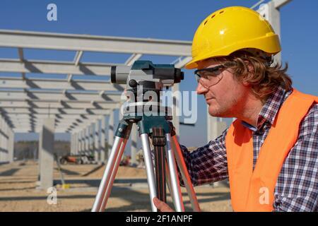 Agrimensor maduro mirando a través de tacheómetro. Trabajador de la construcción en sombrero amarillo frente al edificio Industrial en Construcción.