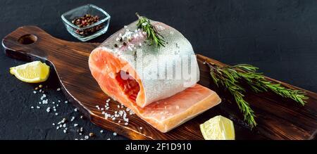 Filete de salmón crudo fresco con limón, corderos y especias en tabla de cortar.