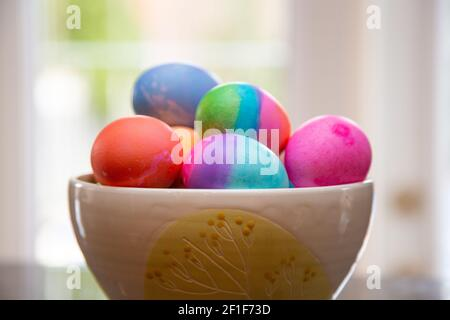 Cuenco de huevos de Pascua de colores brillantes en juego