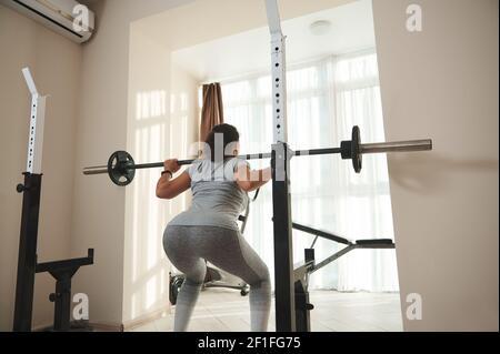 Joven mujer deportiva realizando sentadillas con campana. Entrenamiento en casa.