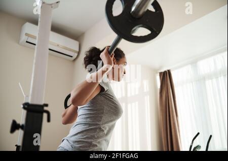 Vista posterior a la joven mujer deportiva africana haciendo escuadrón de servicio pesado en el gimnasio con campana. Culturismo.