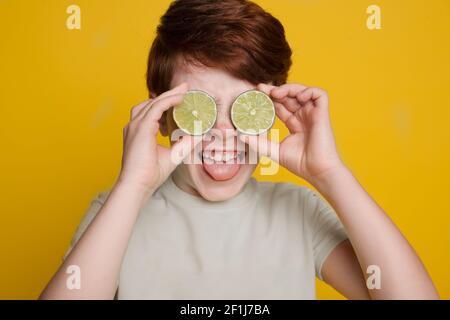 El niño caucásico está cubriendo su ojo con la cal cortada posando en una pared de estudio amarilla