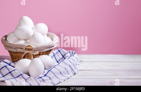 Huevos de pollo blancos en una cesta de paja sobre un fondo azul claro con un trozo de tela, huevos de pollo frescos crudos en un contenedor de papel, producto natural