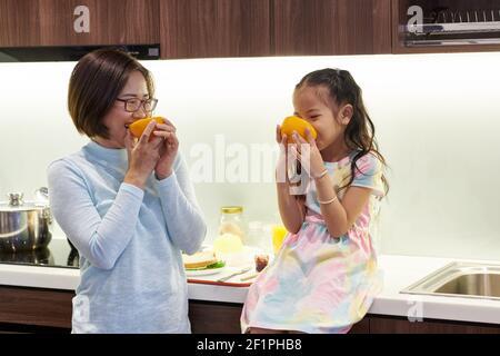 Feliz madre vietnamita y su hija pequeña comer deliciosa jugosa naranjas en kichen para el desayuno