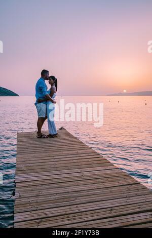 Creta Grecia, joven pareja romántica en el amor está sentado y abrazando en el muelle de madera en la playa en la hora del amanecer con el cielo dorado.