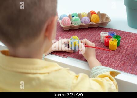 Creadora Caucásica niño pintando huevos de Pascua. Niño preescolar decorar y pintar huevos de pascua en diferentes colores. Preparación para la fiesta EAS