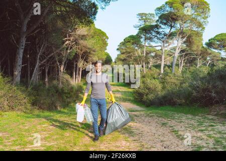Hombre voluntario con bolsa de basura limpiando el bosque de plástico contaminación