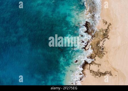 Vista aérea del océano turquesa y rocas de coral en Hawai