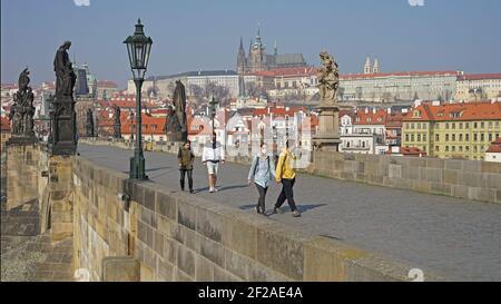 Praga, República Checa - Marzo 20 2020: Coronavirus covid-19 imagen del Puente Carlos vacío con los turistas usando máscara protectora