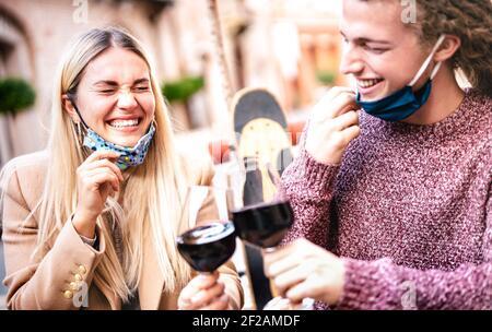 Pareja joven enamorada usando máscaras de cara abierta y teniendo Diversión en el bar de bodega al aire libre - felices amantes de la hipster toasting vino en el patio del restaurante
