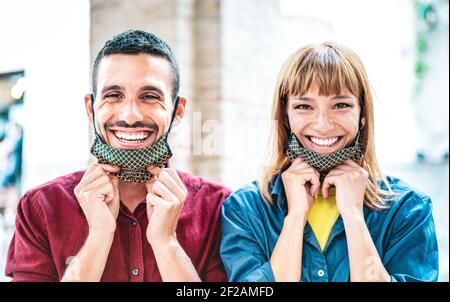 Feliz pareja en el amor sonriendo con máscara abierta - Nuevo estilo de vida normal y el concepto de relación con los jóvenes humor positivo después de bloqueo