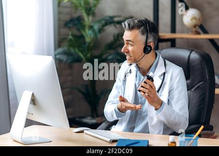 Médico masculino amigable con un abrigo de laboratorio y auriculares hablando por video llamada usando computadora con paciente, consulta en línea. Concepto de ayuda médica remota