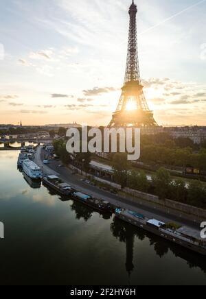 Perfecto Aerial de Amanecer Dorado a través de la torre Eiffel desde las orillas del río Sena, París, Francia. Una torre en el Campo de marte