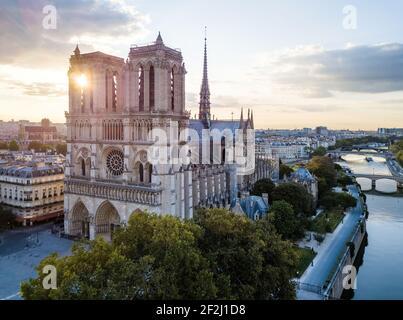 Vista aérea por la mañana de la catedral católica medieval de Notre Dame a orillas del río Sena, París, Francia. Sol escondido detrás de las torres de la iglesia