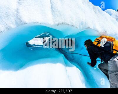 Hiker preparándose para escalar en túnel de hielo en el Glaciar Fox, Isla Sur, Nueva Zelanda. Concepto de expedición de adrenalina y aventura.