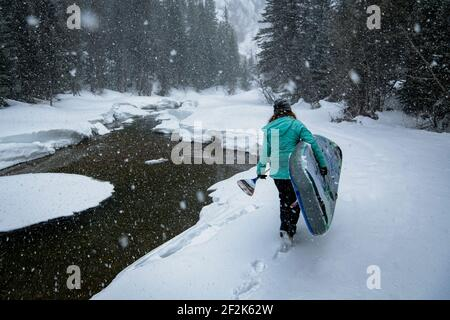 Vista trasera de la mujer llevando tabla de remo mientras camina por el campo de nieve